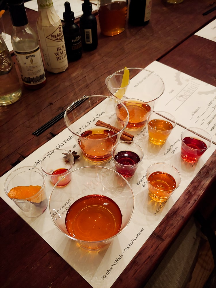 a tasting mat with numerous fillled glasses on it