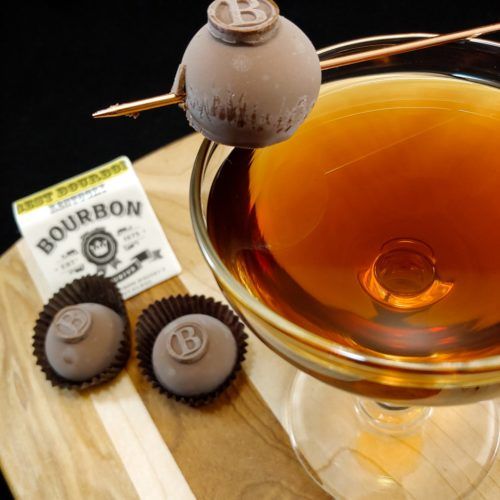 cocktail garnished with chocolate truffle on a wooden board