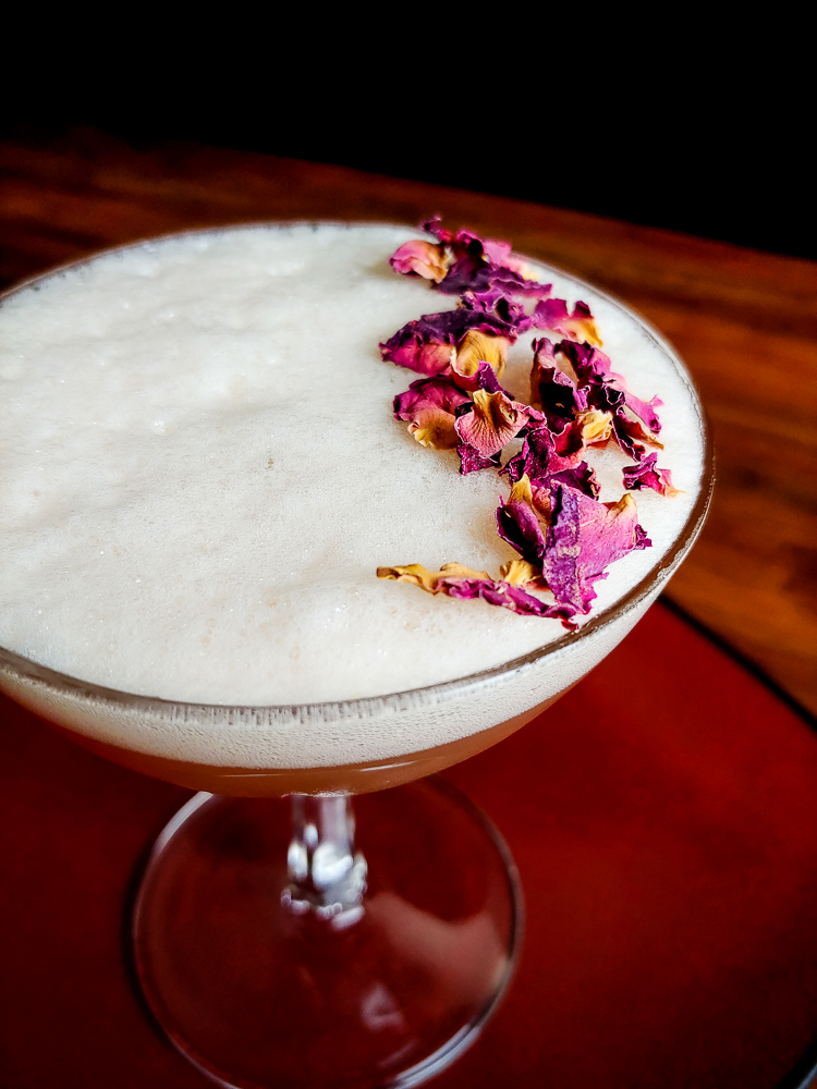 cocktail topped with foam and dried flowers