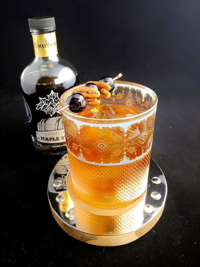 old fashioned glass with drink and bottle of maple syrup