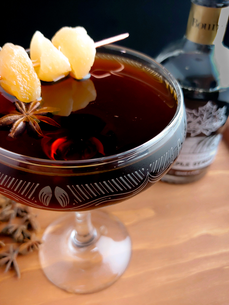 dark cocktail in a coupe glass in front of a bottle of maple syrup