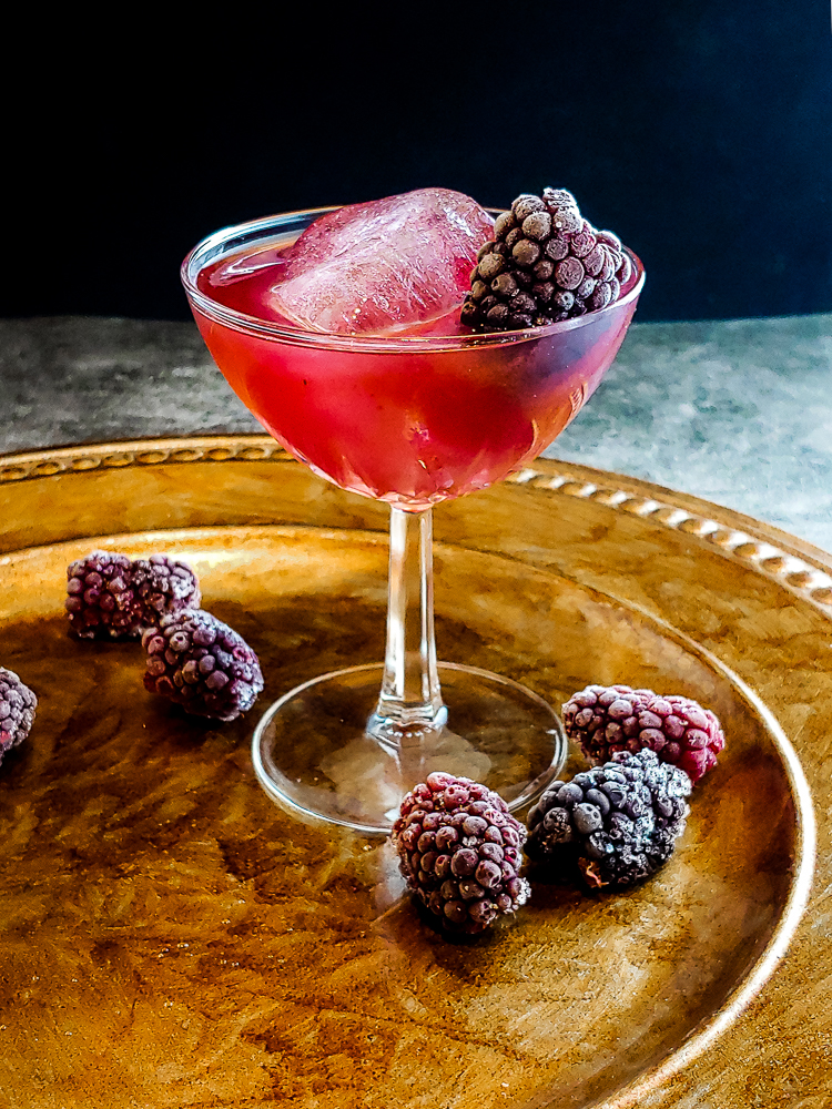 pink cocktail in a glass with ice and blackberry