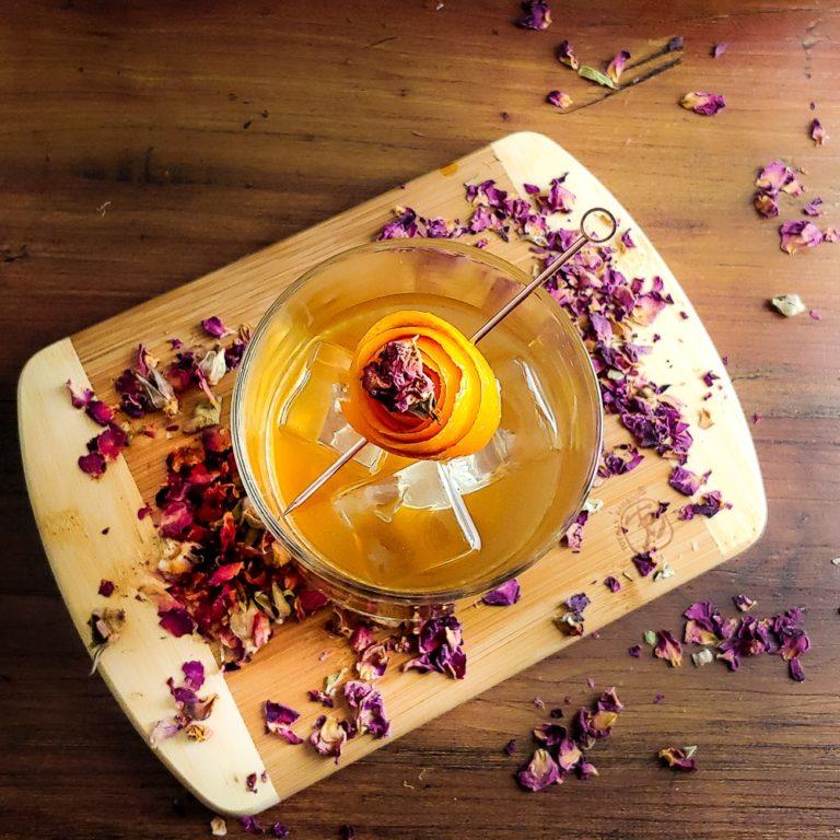Honey Rose Old Fashioned on the rocks with orange rose garnish