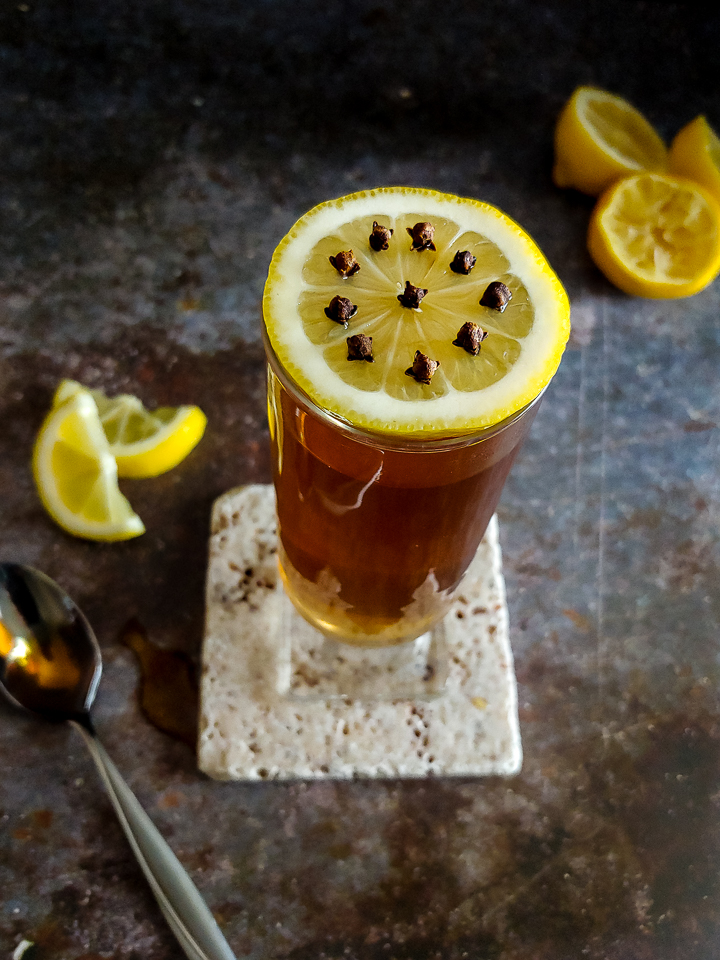 warm cocktail in a glass with a lemon wheel garnish, spoon and lemons