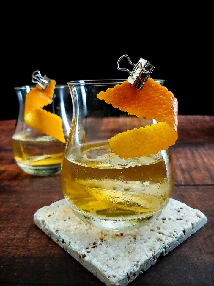 tequila cocktail with orange garnish