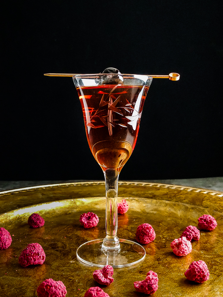 Irish Manhattan on a gold platter with raspberries