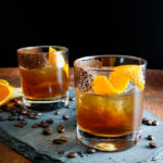 two cocktails with orange garnish