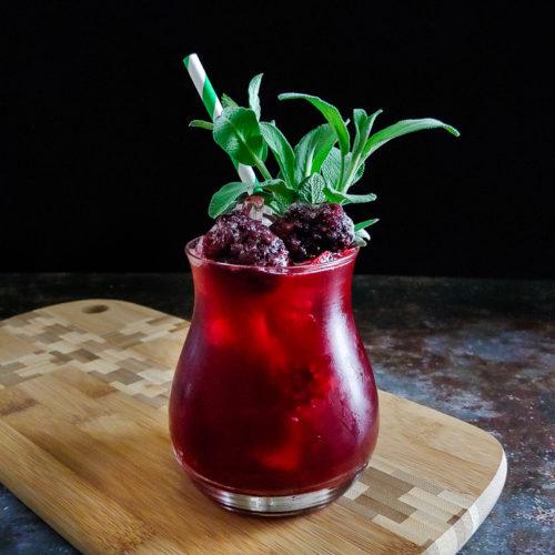 magenta cocktail garnished with sage