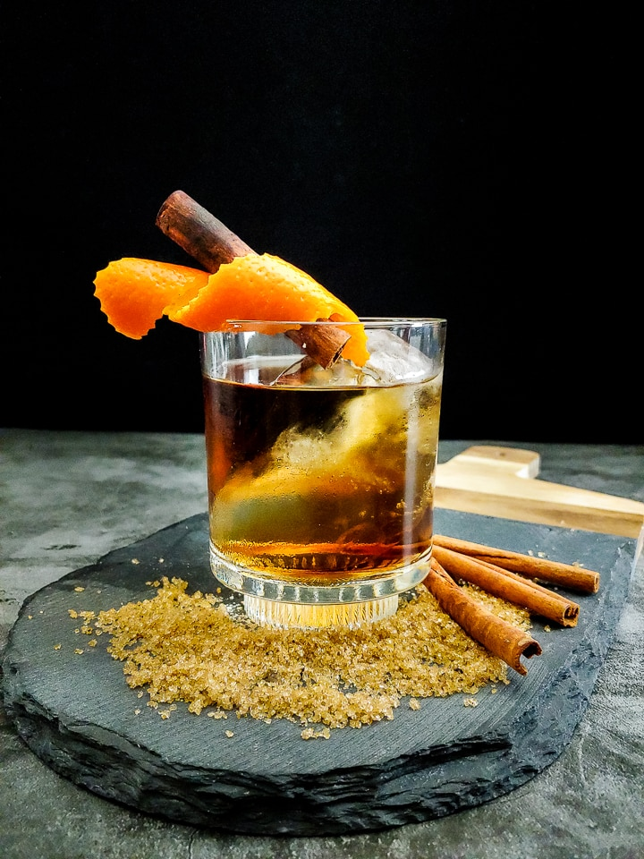 old fashioned cocktail with orange and cinnamon garnish