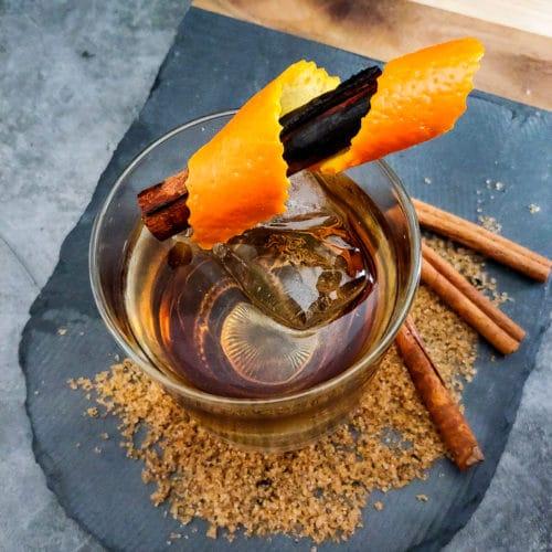 old fashioned cocktail with orange and cinnamon garnish