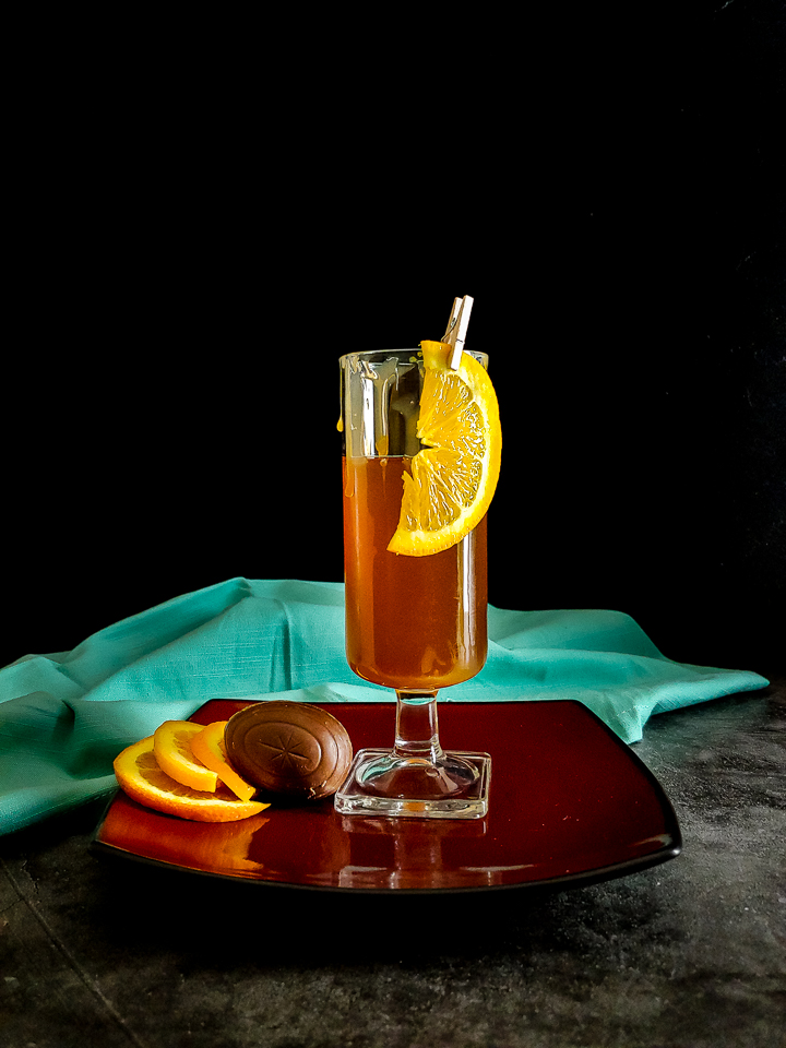 cocktail in a tall glass with whipped cream and orange