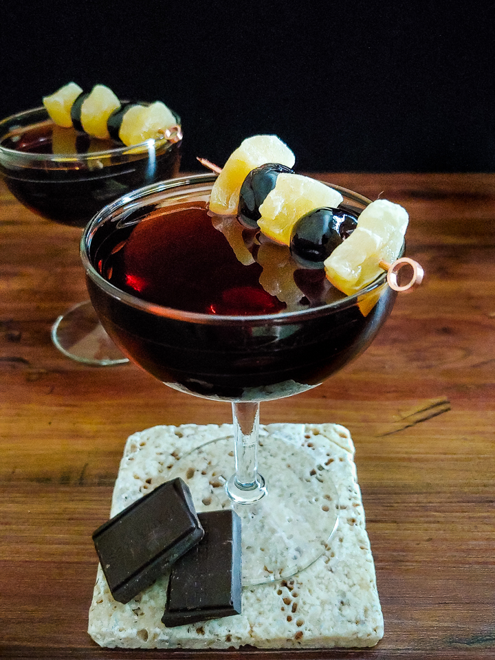 two cocktails in coupe glasses with cherry and ginger garnish