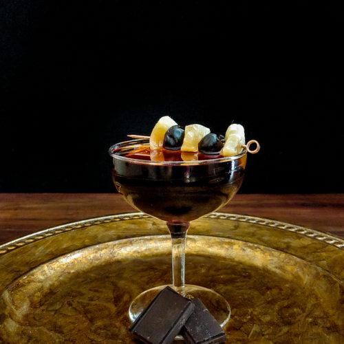 cocktails in coupe glasses with cherry and ginger garnish