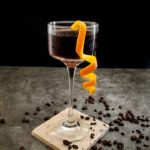 cocktail in glass wih orange garnish