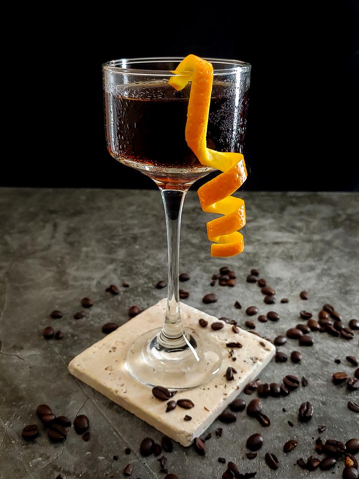cocktail in glass with orange garnish