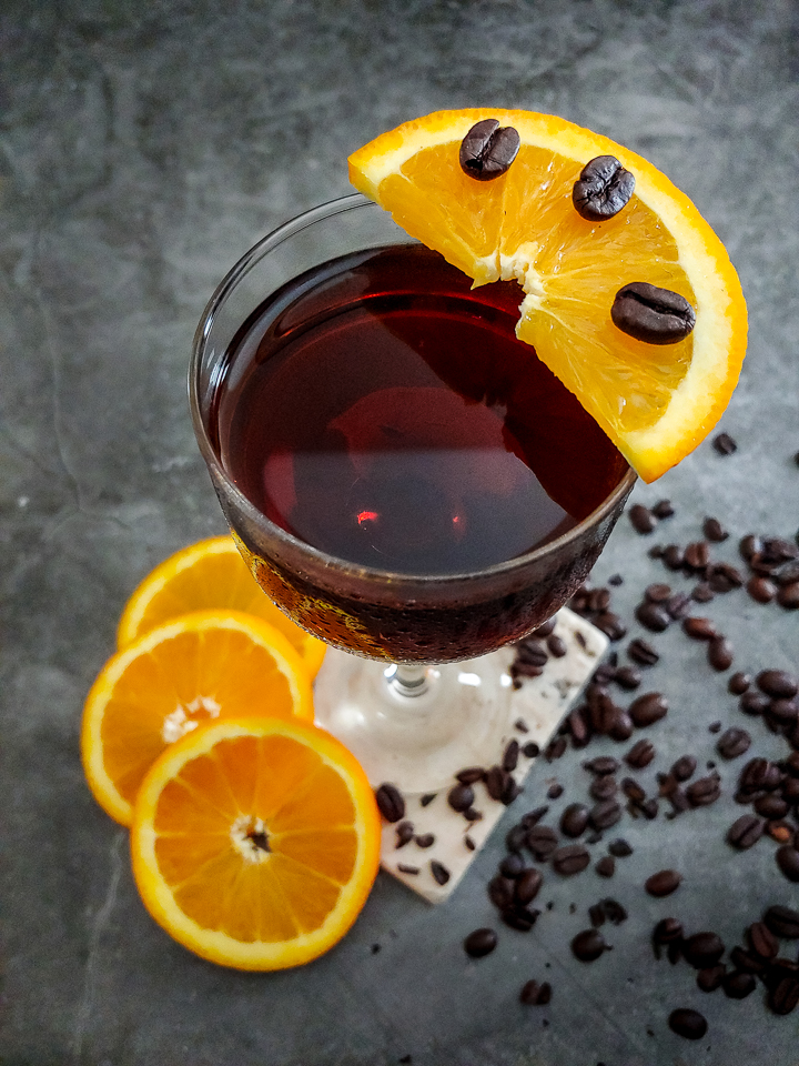 cocktail in glass with orange zest and coffee beans