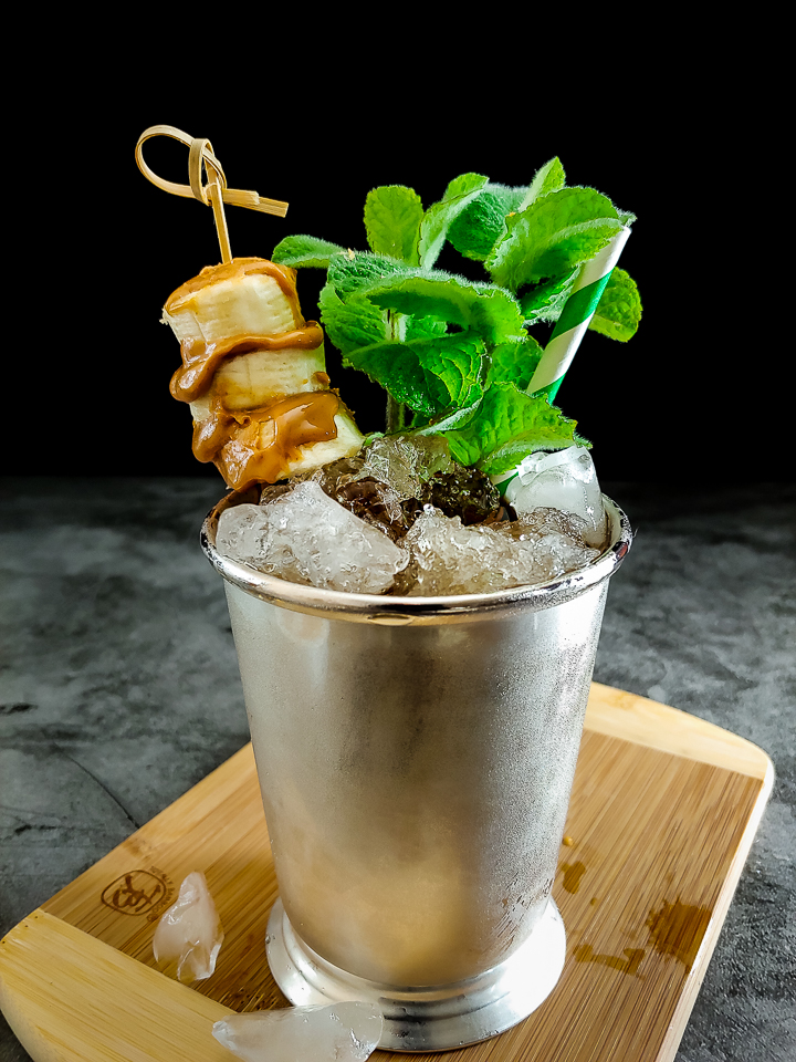 cocktail in julep cup with banana peanut butter garnish