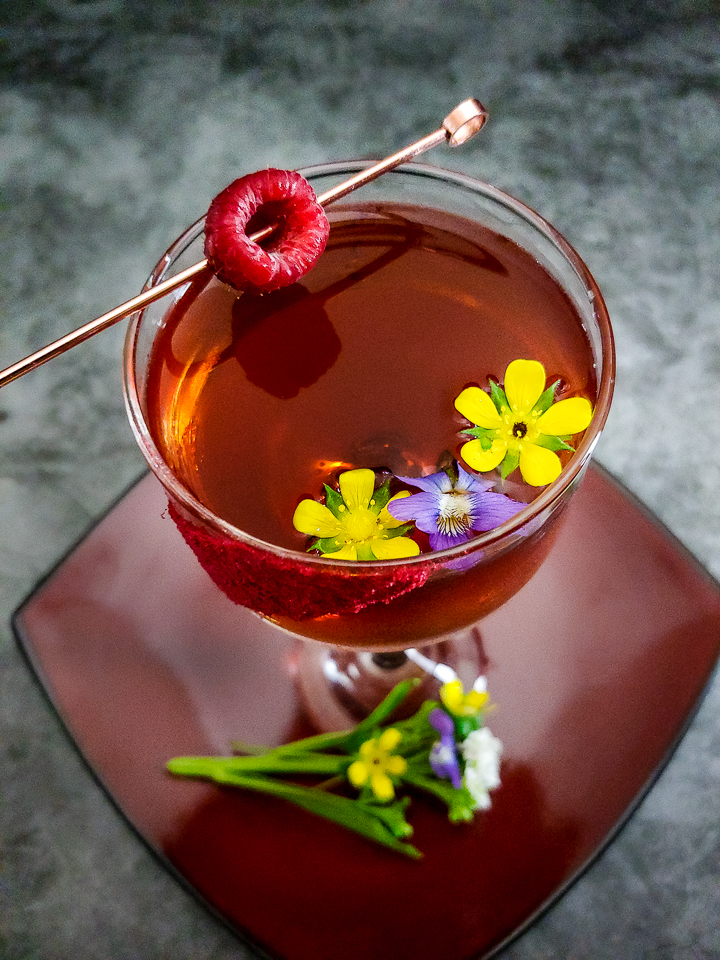cocktail in coupe garnished with flowers and raspberry