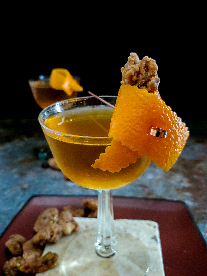 two cocktails in coupe glasses with orange garnish and pralines