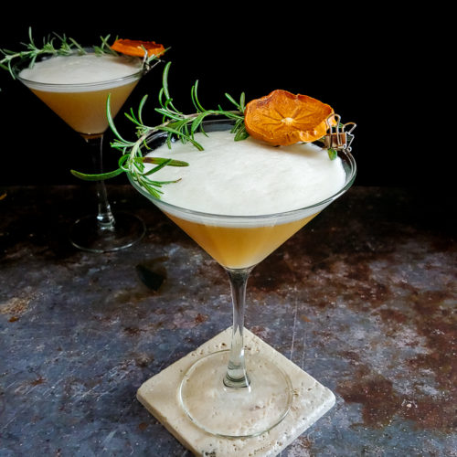 cocktail in martini glass with rosemary and dried persimmon