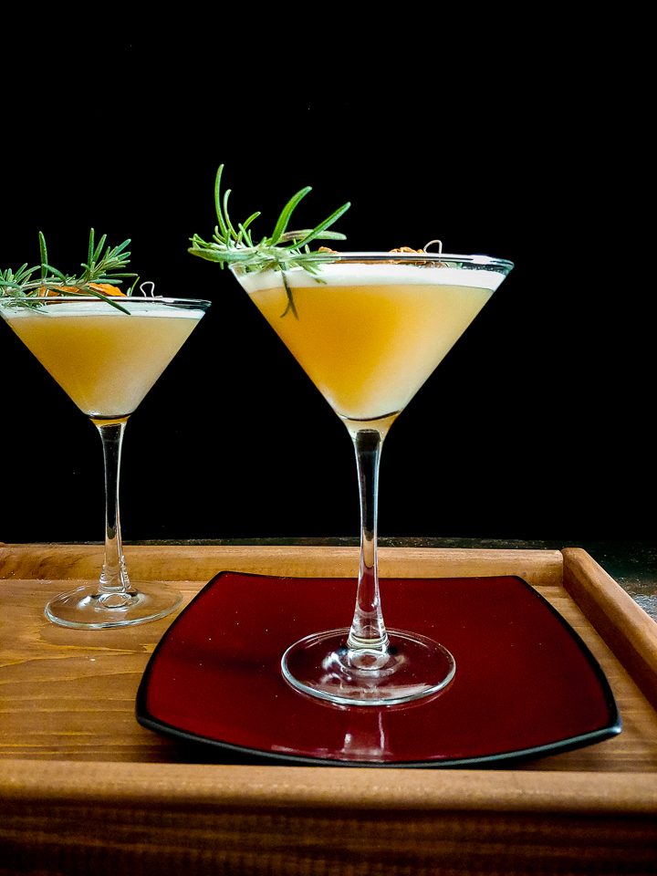 two cocktails in martini glass with rosemary and dried persimmon
