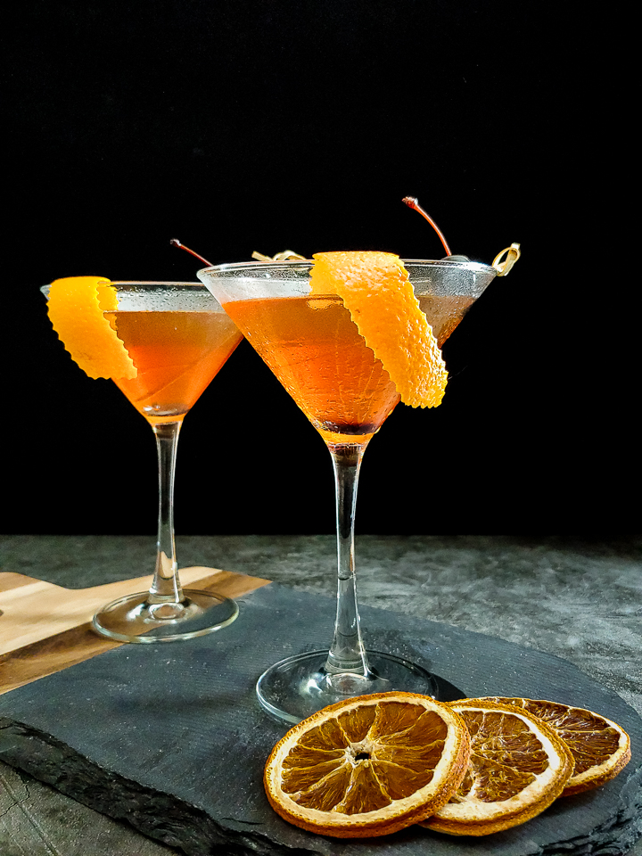 two manhattans with orange garnish