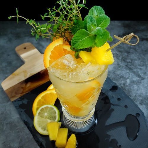 Tiki cocktail with thyme and mint garnish