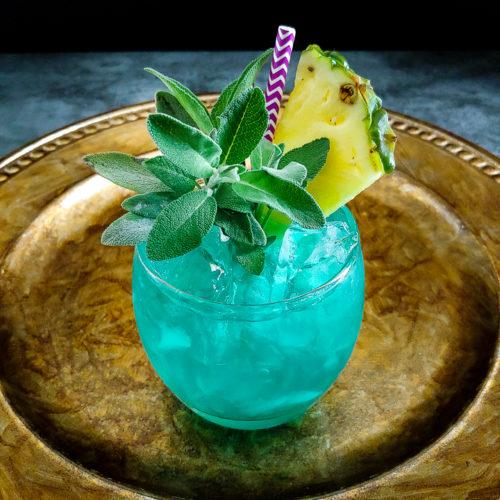 blue cocktail with pineapple sage garnish