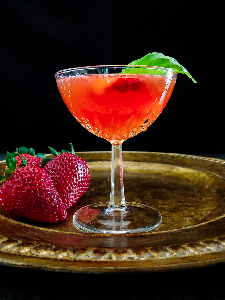 strawberry cocktail in coupe glass with strawberry and basil garnish