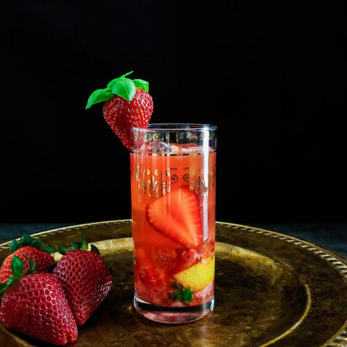 strawberry cocktail in highball glass with strawberry and basil garnish
