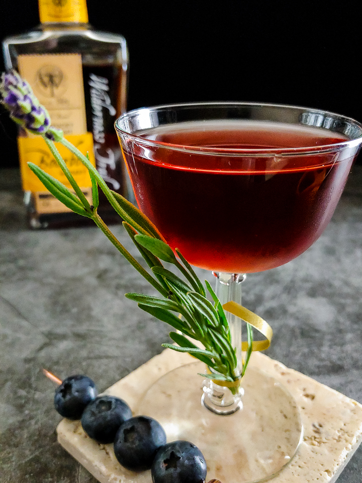 cocktail with lavender and blueberry garnish, Wilderness Trail bourbon in background