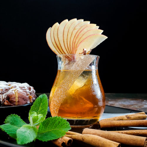 apple fan on whiskey cocktail with cinna mon sticks