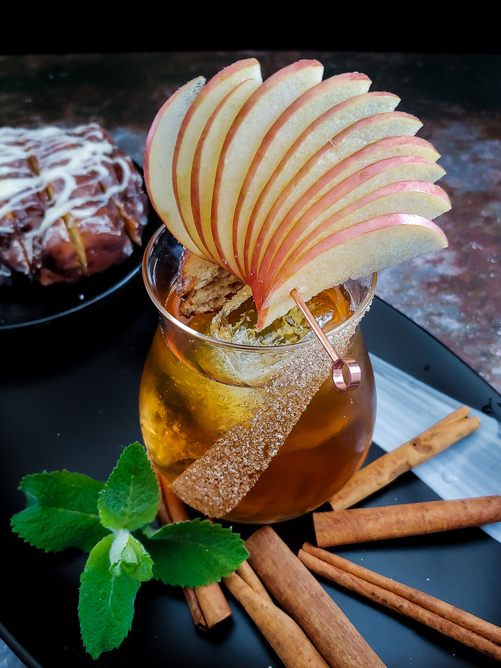 apple fan on whiskey cocktail with cinnamon sticks
