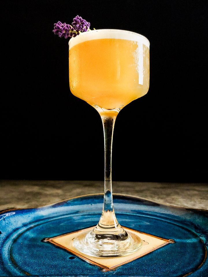 foam topped whiskey sour with lavender sprig