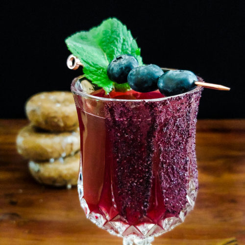 magenta cocktail garnished with blueberries and mint