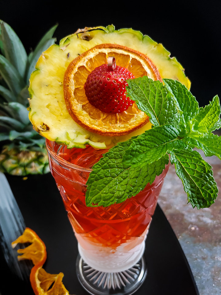 pink tiki cocktail with pineapple round and mint