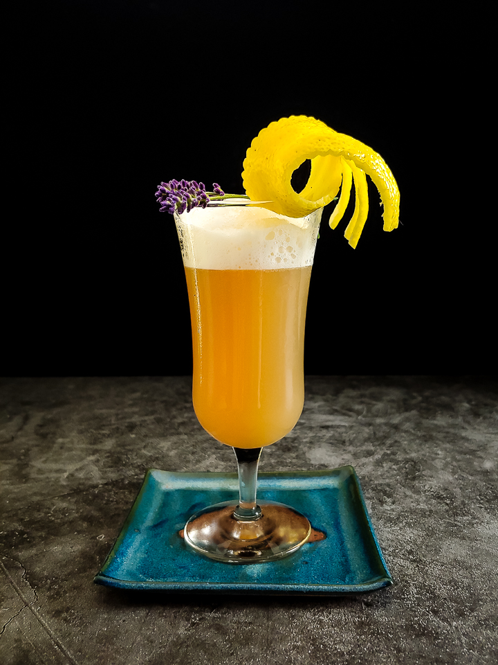rye whiskey sour with lemon and lavender garnish