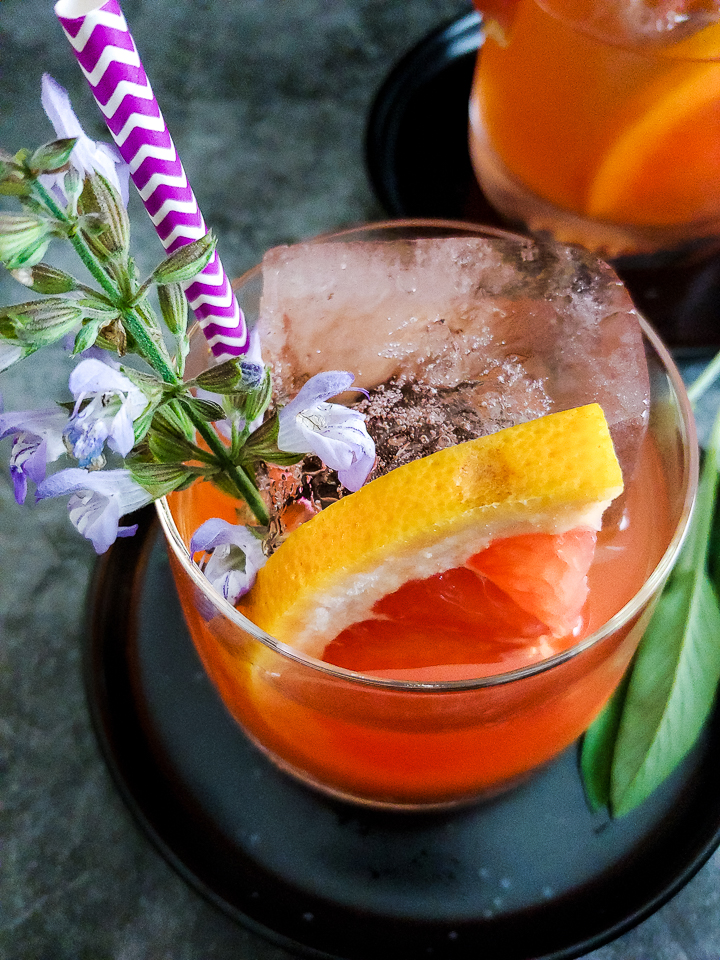 grapefruit mezcal cocktail with grapefuit and sage flower garnish