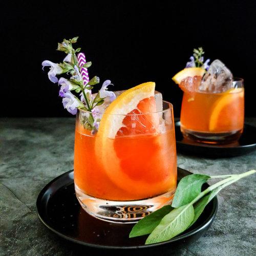 grapefruit mezcal cocktail with grapefuit and sage flower garnish