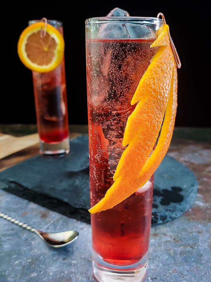 magenta whiskey cocktail in highball glass with orange garnish