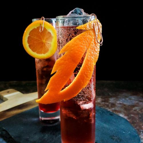 magenta whiskey cocktail in highball glass with orange garnish