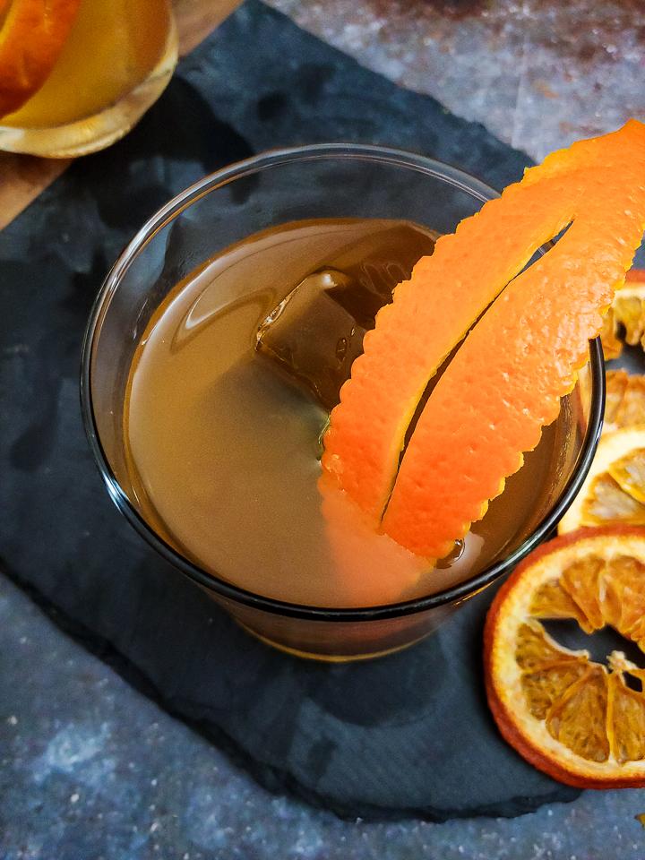 old fashioned cocktail with orange leaf garnish