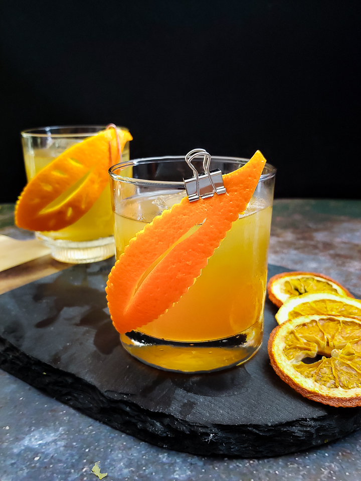 old fashioned cocktail with orange leaf garnish