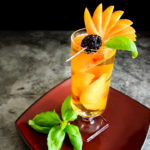 peach and whiskey highball with peach fan and basil garnish