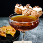 cocktail with donut holes garnish, glazed with icing and candied pecans