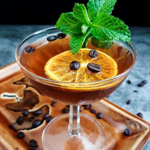rum cocktail with mint and orange chip garnish