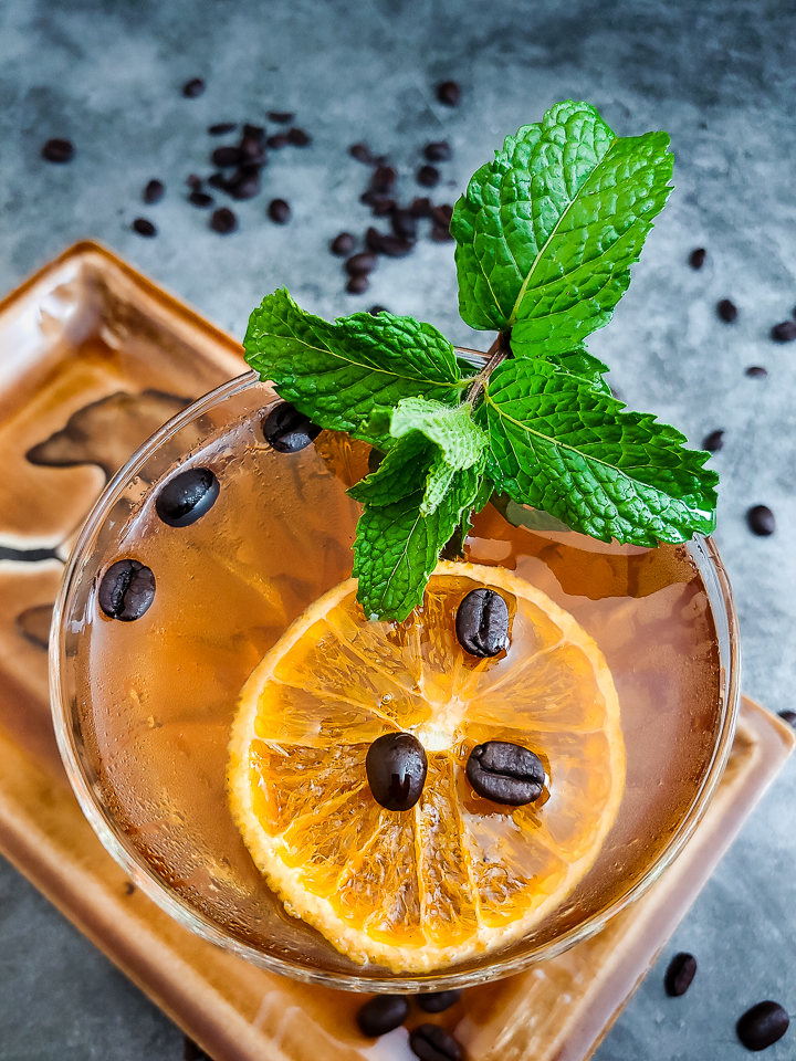 rum cocktail with mint and orange chip garnish
