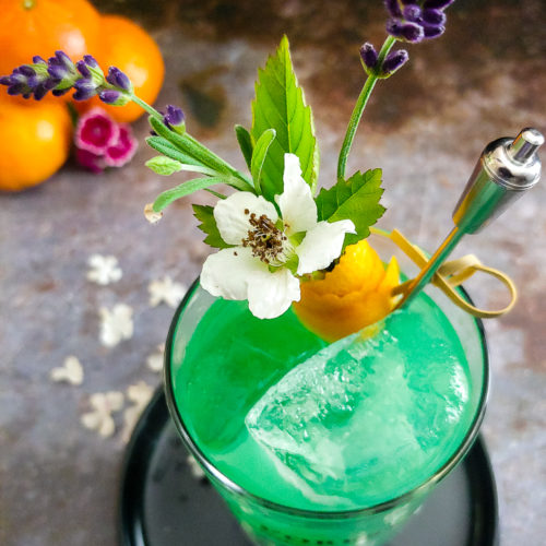 aqua green cocktail in highball glass with orange and lavender garnish