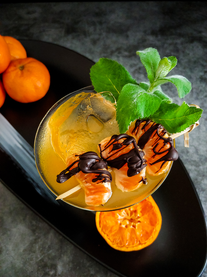 orange-yellow cocktail with ice and chocolate covered mandarins and mint garnish