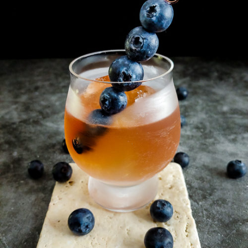 old fashioned in rocks glass with blueberry skewer